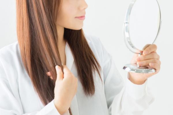 鏡に向かって髪をいじる女性